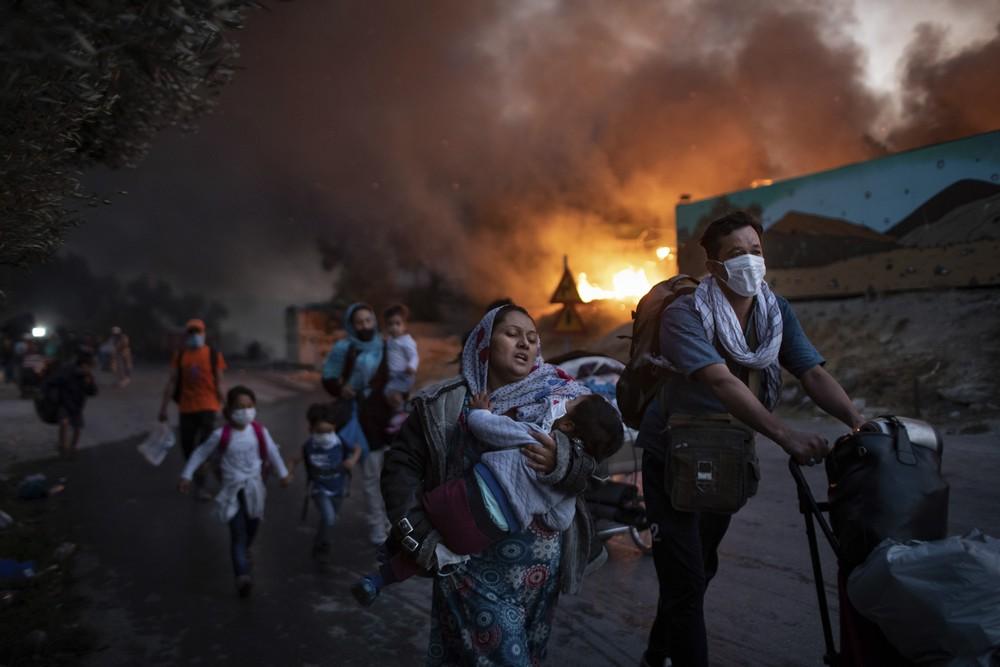 Πρόσφυγες φεύγουν από το ΚΥΤ της Μόριας που έχει πιάσει φωτιά στις 8 Σεπτεμβρίου 2020